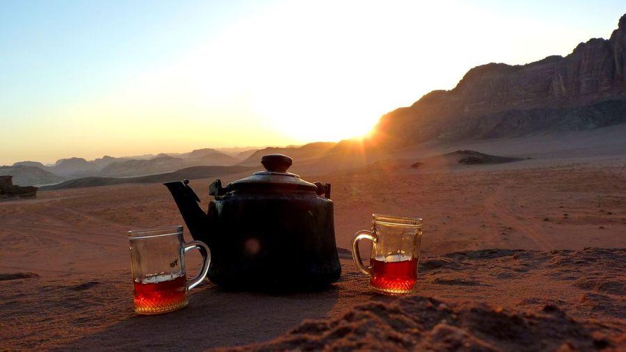 Tea kettle and glasses on desert against sky during sunset