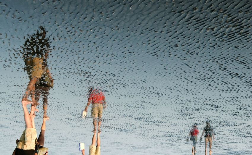 Reflection Of People Walking On Shore