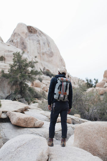 Adventure Backpack Beauty In Nature Casual Clothing Day Exploration Full Length Geology Hiker Hiking Leisure Activity Lifestyles Men Mountain Nature One Person Outdoors Physical Geography Real People Rear View Rock - Object Rock Formation Scenics Standing Tranquil Scene