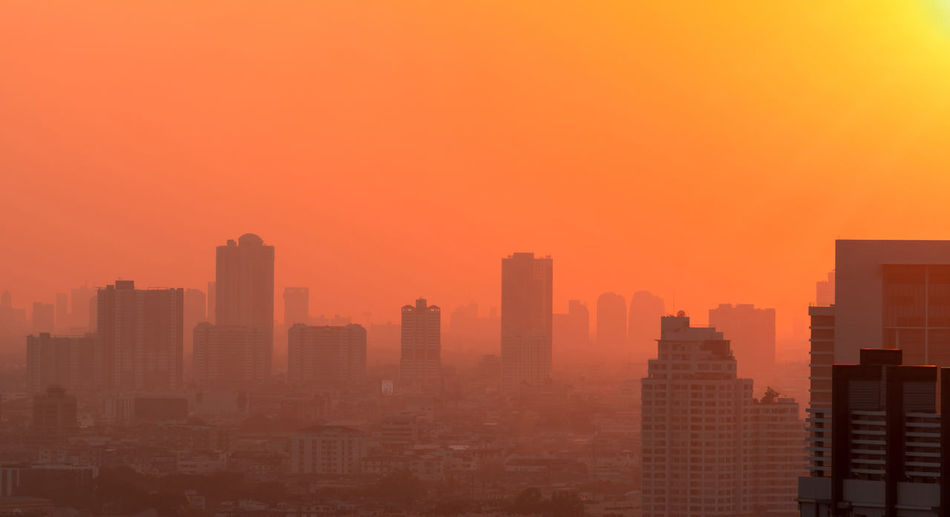 Buildings in city against orange sky