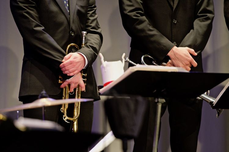 Midsection of men holding wind instruments while standing on stage