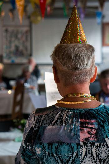 Rear view of senior woman wearing cap at birthday
