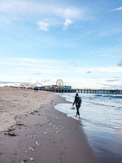 Woman Walking On Sea Shore By Amusement Park Against Sky
