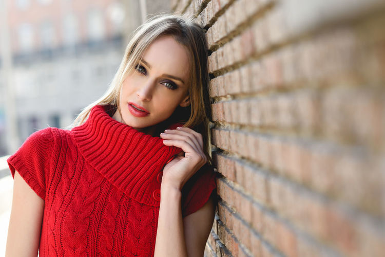 Close-up portrait of young blonde woman standing in the street near a brick wall. Beautiful girl in urban background wearing red dress. Female with straight hair and blue eyes. Brick Wall Fashion Looking At Camera Woman Young Beautiful Woman Beauty Blond Blond Hair Fashion Model Fashion Photography Female Girl Russian Girl Street Style Young Adult Young Girl Young Women