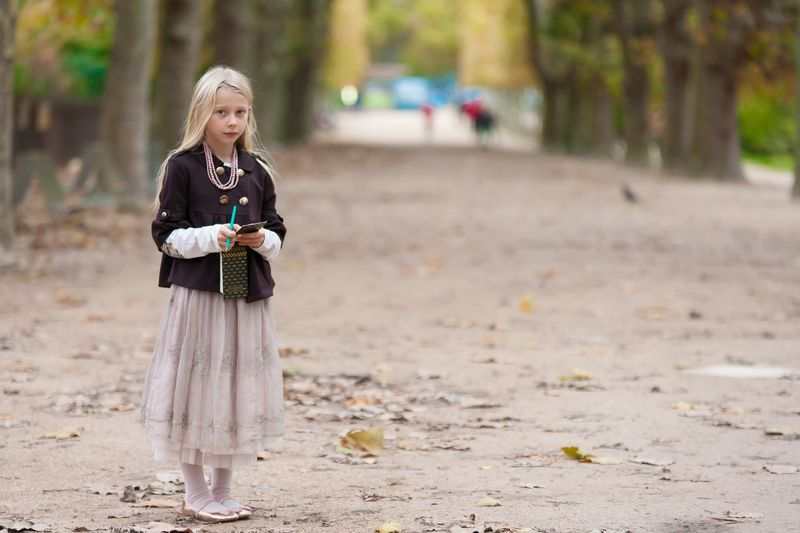 Portrait Of Girl Holding Note Pad And Pen While Standing At Park