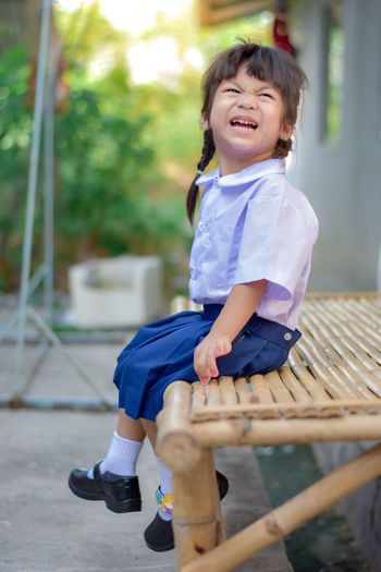 Full length of happy girl sitting outdoors