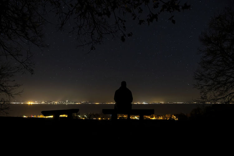Silhouette man sitting on bench against sky at night