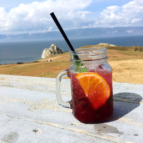 Close-up of drink on glass at beach