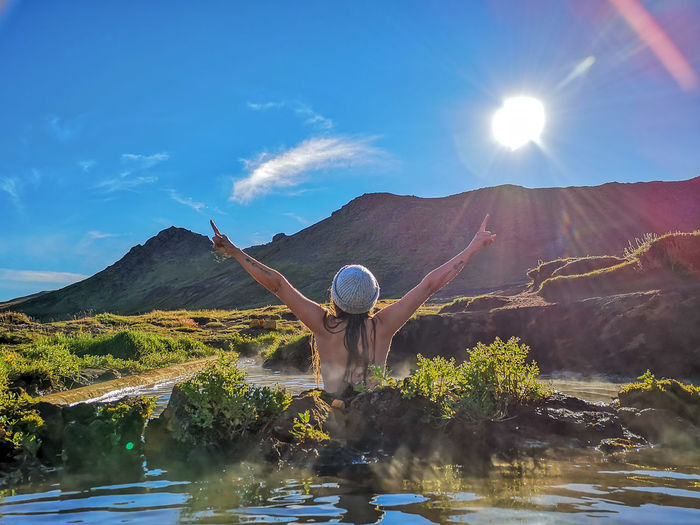 Rear view of woman with arms raised at hot spring against mountain