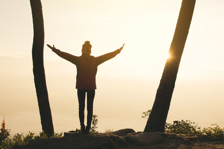 Full Length Of Woman Standing On Cliff With Arms Raised Against Sky During Sunset