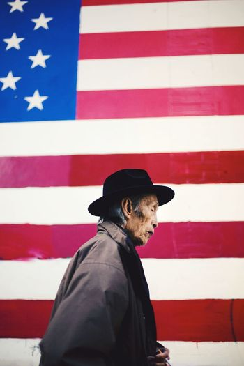 A man passes by an American flag painted on a wall in Chinatown, San Francisco, California. Striped Flag Patriotism Adult One Man Only Red Outdoors Day San Francisco Chinatown San Francisco Chinatown American Flag USA American