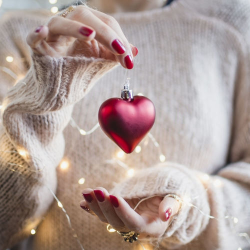 Midsection of woman with illuminated string lights holding red heart shape bauble during christmas