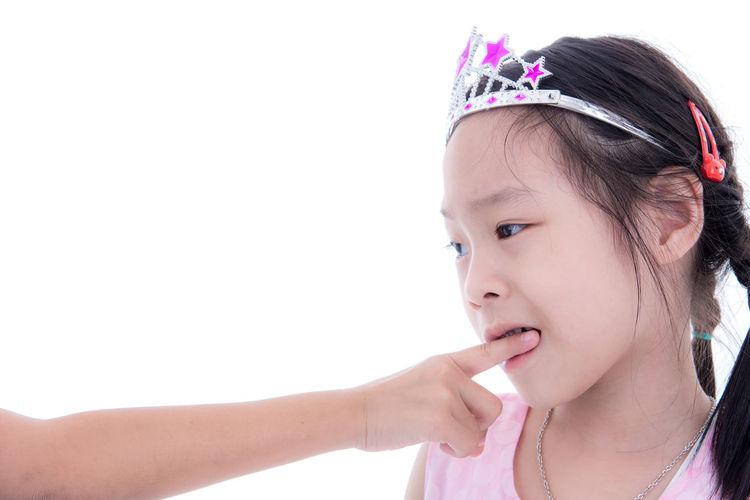 Girl wearing tiara biting cropped hand against white background