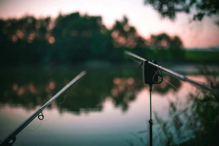 Close-up of fishing rods by lake during sunset