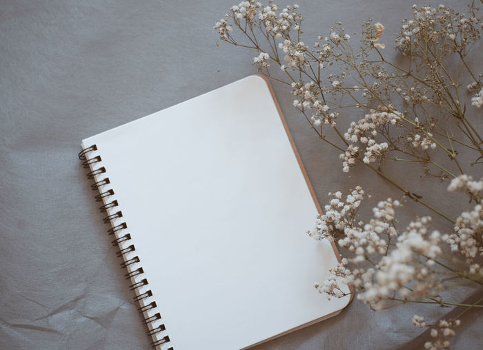Close-up of blank book with flowers on table