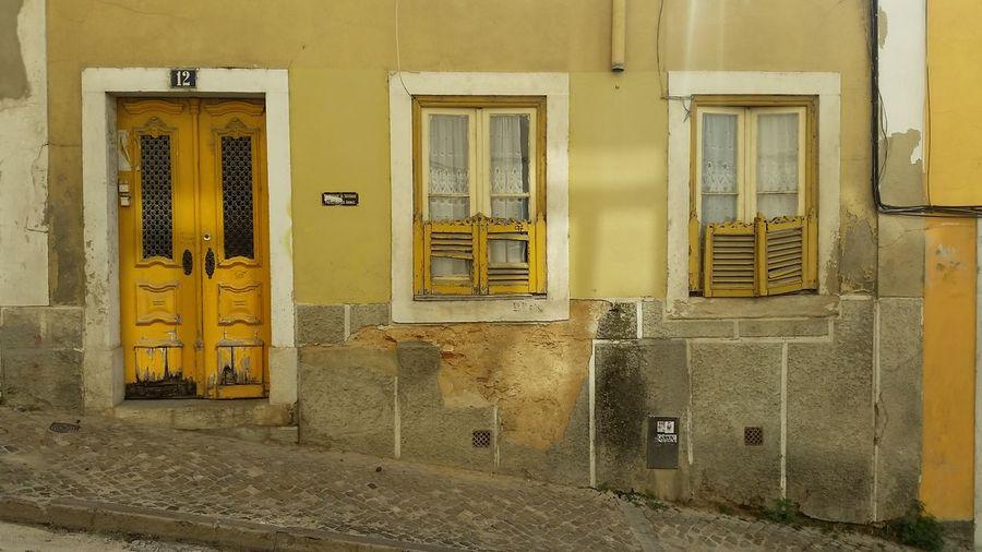 Urbanphotography Urban Geometry Lisboa Yellow Doorway Door Architecture Building Exterior Built Structure Shutter Closed Door Building Exterior Residential Structure