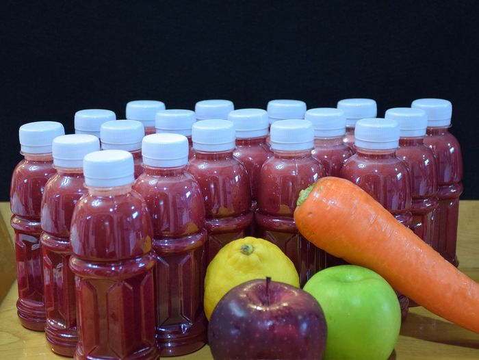 Close-up of fruits and vegetables with juice on table