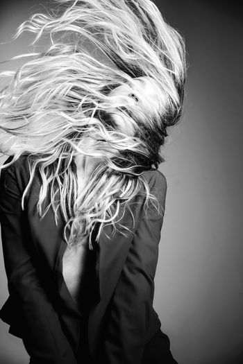 Woman tossing hair against gray background