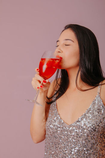 Young woman drinking glass against white background