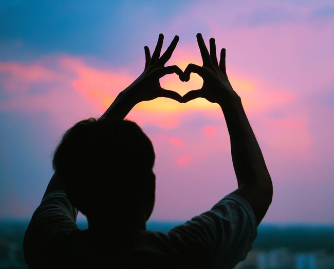 Sunset Man Sunset Sky Real People Silhouette Arms Raised Heart Shape Human Arm Gesturing One Person Lifestyles Making Leisure Activity Positive Emotion Rear View Nature Love Emotion Headshot Cloud - Sky Outdoors Hand Finger Hand Raised