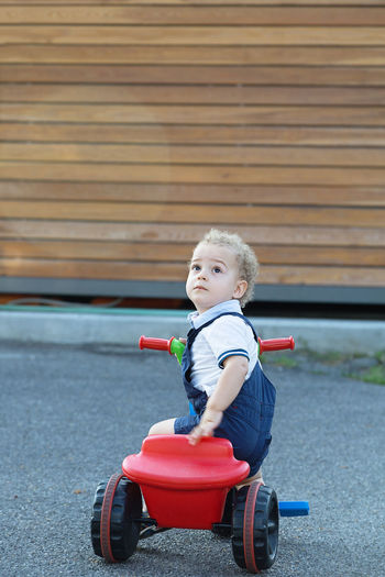 Cute Boy Looking Up While Sitting On Tricycle