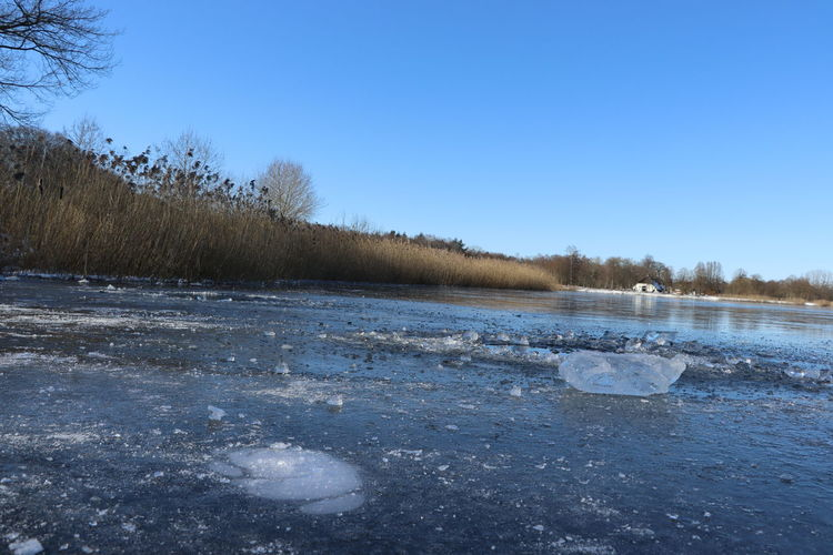 Frozen lake against clear sky during winter