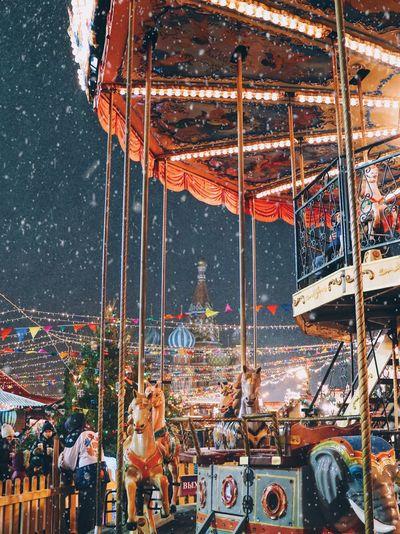 Carousel in amusement park against sky at night