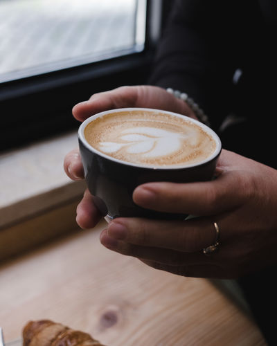 Cropped hands holding coffee cup