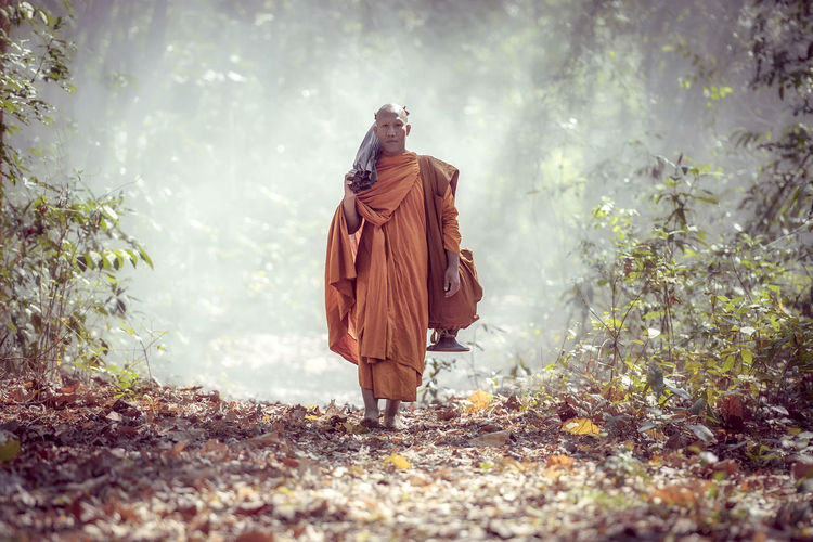 Full Length Of Monk Standing On Field At Forest