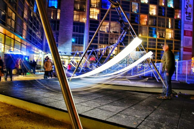 Swing Child Childhood Illuminated City Architecture Street Night Motion Light Trail Long Exposure Speed People Building Exterior Modern Playground Joy