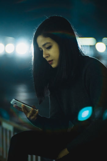Young Woman Using Phone At Night