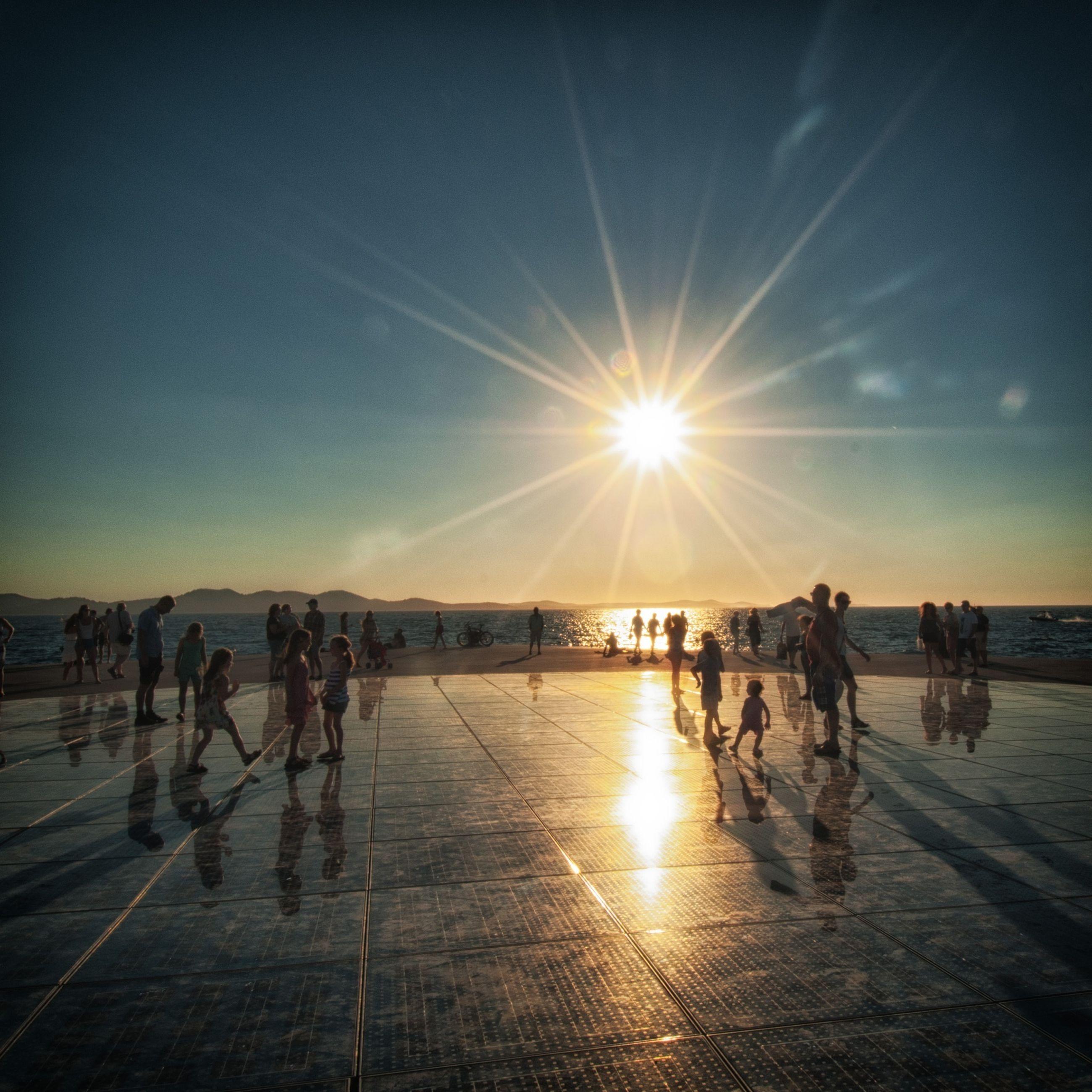 water, sun, beach, large group of people, sea, lifestyles, leisure activity, mixed age range, shore, sunlight, enjoyment, horizon over water, men, vacations, sunbeam, person, sunset, enjoying, medium group of people