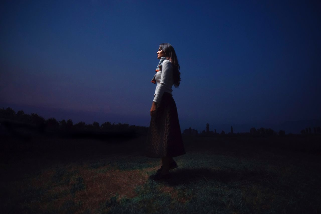 Side view of young woman standing on grassy field at night