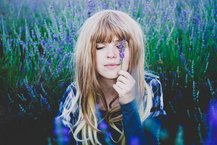 Beautiful young woman holding lavender flowers over eye while sitting in lavender field