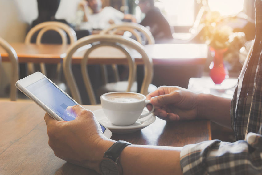 Male using a smart phone with coffee cup on wooden table. Holding Cup Mug Coffee Cup Real People Human Hand Drink Coffee - Drink Coffee Hand Food And Drink Refreshment Cafe Leisure Activity Lifestyles Men Human Body Part One Person Wireless Technology Connection Coffee Shop