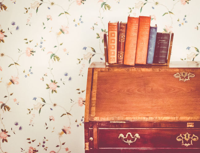Old fashioned writing desk with books stored on top of it. Holy Bible Old Fashioned Patterned Wallpaper Reading Writing Writing Desk  Book Book Shelves Bureau Close-up Diary Drawers Floral Wallpaper Home Interior Indoors  No People Old-fashioned Religious  Vintage Vintage Photo Wallpaper Wood - Material