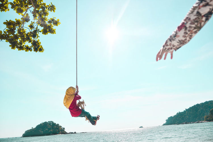 Low angle view of girl on rope swing over ocean