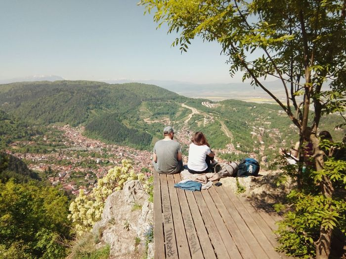 Rear View Of Man And Woman Sitting On Observation Point Against Sky