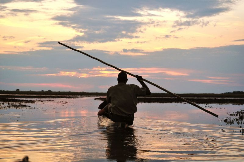 Silhouette Fisherman Rowing Boat With Bamboo In Lake During Sunset