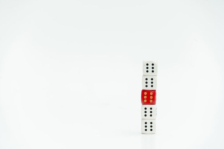 Diversity White Background Studio Shot No People Copy Space Indoors  Gambling Arts Culture And Entertainment Number Control Leisure Games Relaxation Close-up Remote Control Single Object Leisure Activity Opportunity Luck Red White Color Technology Small Group Of Objects