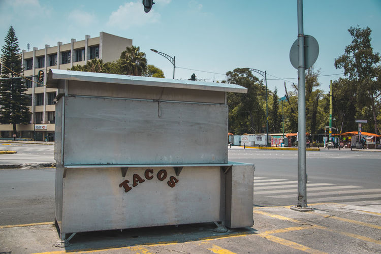 Taco stand on street against sky in city