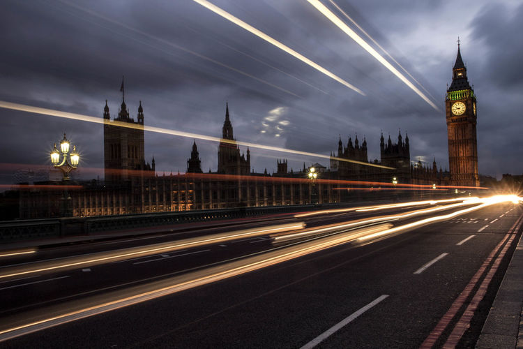 Light Trails On Westminster Bridge By Big Ben Against Cloudy Sky At Dusk
