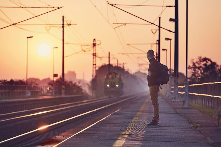 Alone man with backpack waiting at railroad station platform at sunrise. Man People Passenger Waiting Standing Real People Rail Transportation Railroad Track Railroad Station Railroad Station Platform Railway Train Sunrise Sun Sunset Moody Sky Sky Transportation One Person Lifestyles Lonely Loneliness Alone Backpack Connection