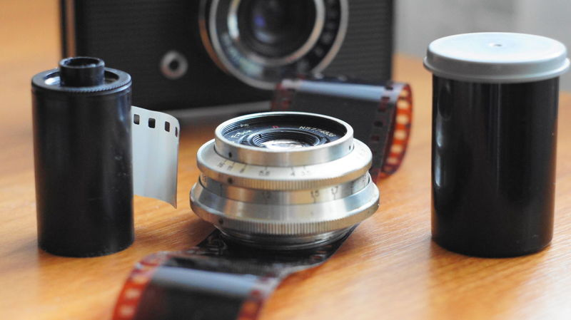 A still life of accessories from old film cameras: camera, lens, film cassette, piece of film, film container. 70's Style Camera - Photographic Equipment Close-up Day Indoors  Lens No People Photography Themes Spool Table Technology