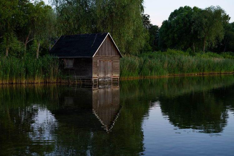 House by lake against trees