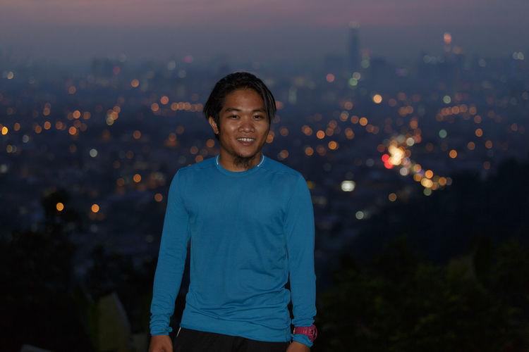 Portrait of smiling man standing against illuminated city at dusk