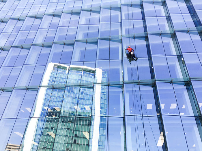 Low angle view of man cleaning modern building