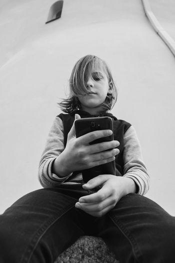 Full length of longhaired  boy using mobile phone