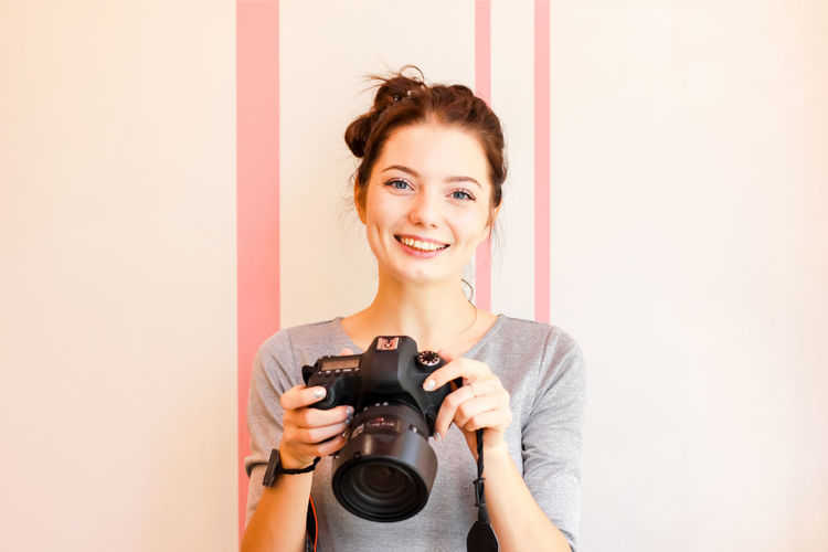 Pretty girl photographer looks at camera and smiles Activity Adult Beautiful Woman Beauty Camera - Photographic Equipment Digital Camera Emotion Front View Hairstyle Happiness Holding Indoors  Looking At Camera One Person Photographer Photographing Photography Themes Portrait Smiling Technology Women Young Adult Young Women