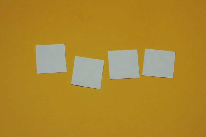 Close-Up Of Empty Sticky Notes On Yellow Wall